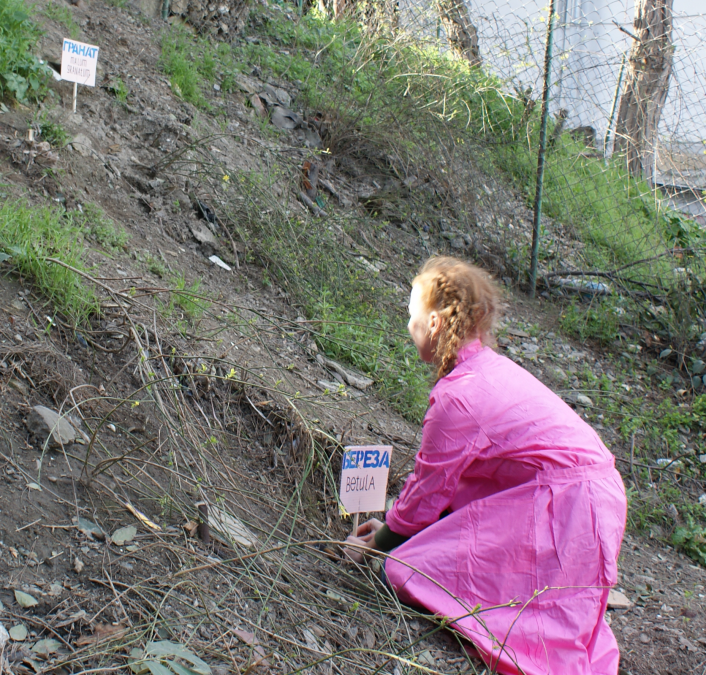 A woman in a pink bathrobe holds a tablet with the name of the plant at the foot of the hill